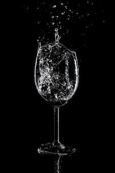 Всплеск воды в стакане на черном фоне