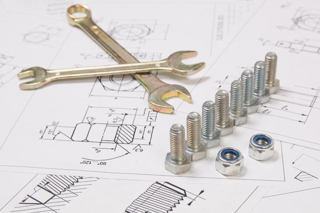 Гаечный ключ, болты и гайки над инженерными чертежами. наука, механика и машиностроение