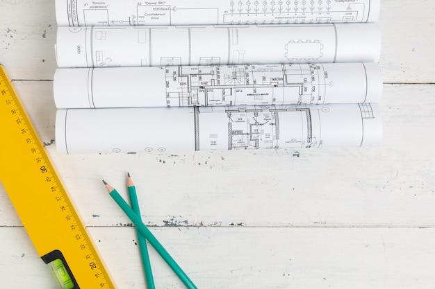 Уровень строительства, чертежи, чертежи и карандаши на белом столе