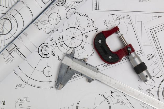 Штангенциркуль, микрометр и технические чертежи промышленных деталей и механизмов