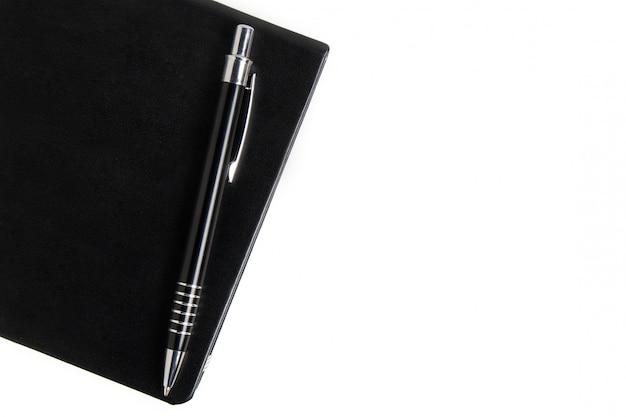 黒いノートと白い背景の上のペン。コピースペースのビジネスコンセプト