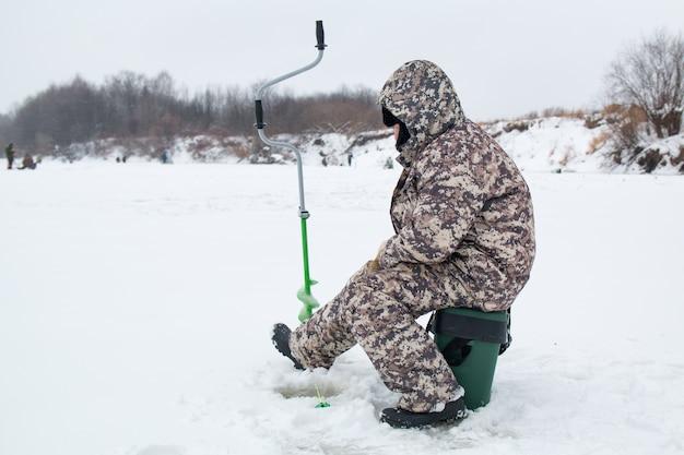 冬の釣り。冬の川での釣りの氷の漁師。