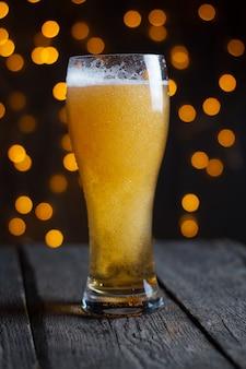 暗いテーブルの上のガラスのビール