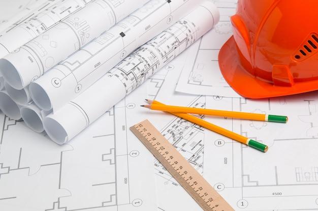 紙の建築図面、青写真、鉛筆、定規、ヘルメット。エンジニアリング設計図
