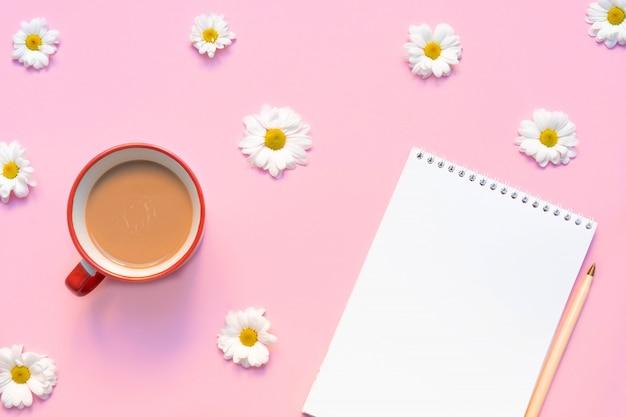 コーヒーマグカップ、ペン、およびパステルピンクの背景に花と空のノートブック。夏または春の組成。コピースペース、トップビュー、フラットレイアウトの画像