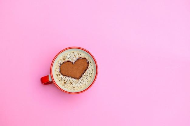 柔らかいピンクの背景にハート形のカプチーノコーヒーカップ。おはようコンセプト。コピースペース、トップビューの画像