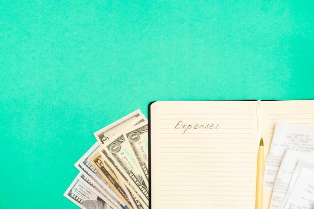 経費会計の概念。ドル紙幣、領収書、ペン、メモ帳のビューのすぐ上に手書きの単語が緑の背景、コピー領域の費用