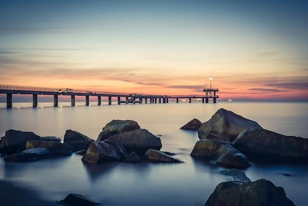 Восход солнца над морским мостом в бухте бургаса. винтажный эффект.