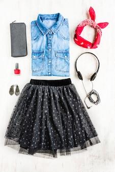 女性服の平面図です。女性のタルスカート、デニムシャツ、アクセサリーのコラージュ。ファッショナブルな都市服。