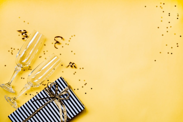 Вид сверху двух хрустальных бокалов для шампанского, подарочной коробки и золотого конфетти в форме звезды на желтом