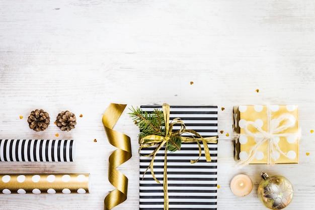 Подарочные коробки, обернутые в черно-белую полосатую и золотую пунктирную бумагу с сосной, шишками, свечами и оберточными материалами на белом фоне старого дерева. подготовка рождественских подарков. пустое пространство.