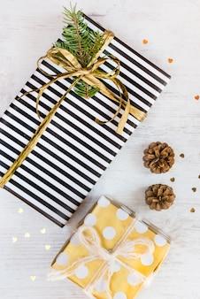 Вид сверху подарочных коробок, обернутых в черно-белую полосатую бумагу с золотыми точками и соснами