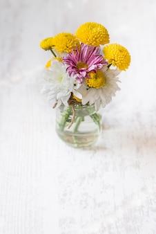 白い木の素朴な背景の上の瓶花瓶に春の花ブーケ