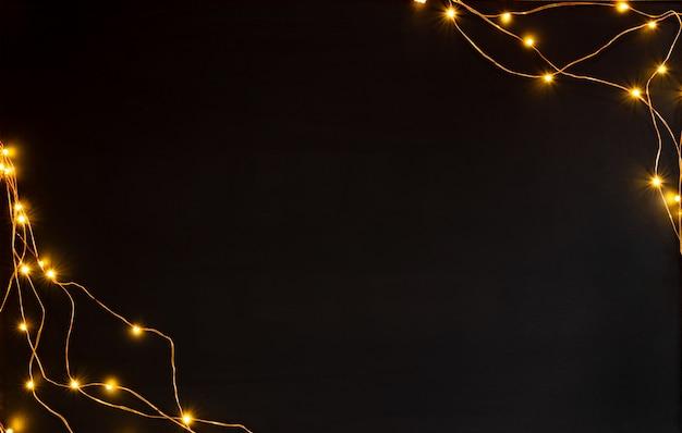 白い背景の上のクリスマスライトガーランドの境界線。