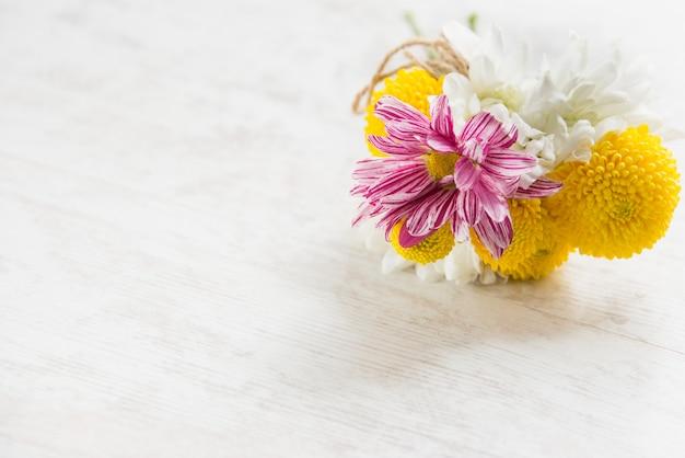白い木の素朴な背景の上の新鮮な花の花束