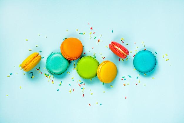 Разноцветные миндальные печенья, расположенные как радуга на синем