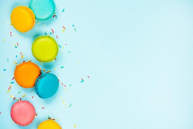 カラフルなマカロンと砂糖を振りかける青い背景に配置の平面図です。