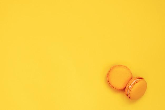 黄色の背景に黄色のマカロンの平面図です。スペースをコピーします。