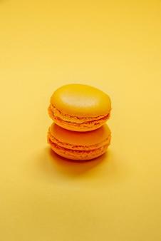 Вид сверху красочных миндальное печенье, сахарных брызг и партийных лент, расположенных на желтом