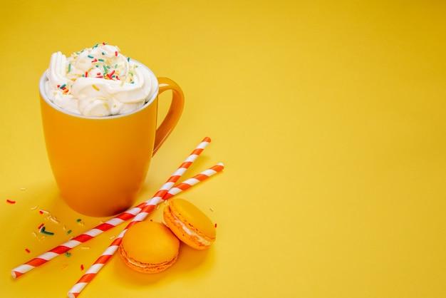 黄色のコーヒーカップ、ストロー、黄色のフランスのマカロンのクローズアップ