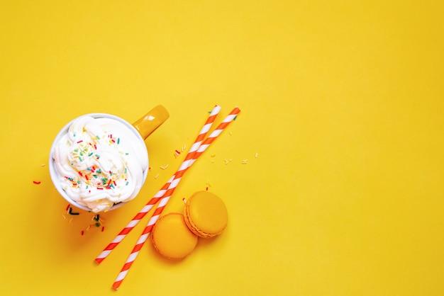 黄色の黄色のコーヒーカップ、ストロー、フランスのマカロンのトップビュー