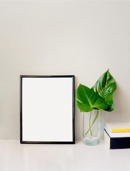 Черная рамка для фотографий, зеленое растение в хрустальной вазе и куча книг, расположенных против пустой серой стены
