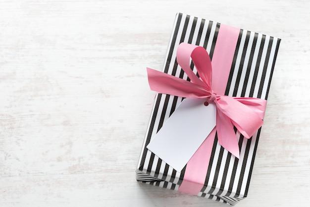 白の木製の古い背景にピンクのリボンと黒と白の縞模様の紙で包まれたギフトボックス