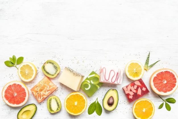 柑橘系の果物、ハーブ、チアシード、アロエを配置したさまざまなカラフルな手作り有機石鹸の平面図です。