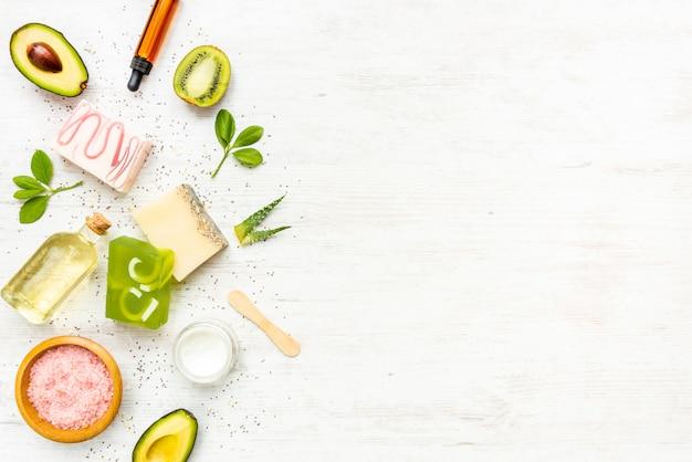 果物、ハーブ、チアシード、アロエ、エッセンシャルオイルで整理された有機石鹸と化粧品の平面図。