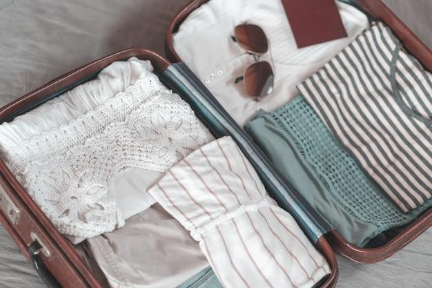 Летняя женская одежда аккуратно сложена для упаковки в чемодан. туристический чемодан готовится.