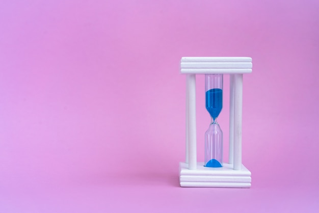 コピーとピンクの背景に青い砂を実行しているエレガントな砂時計