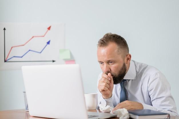気分が悪く、疲れている。オフィスで働く熱いお茶のカップを持つ男、ビジネスマンは風邪、季節性インフルエンザをキャッチしました。