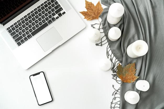 Рабочее пространство стола домашнего офиса с мобильным телефоном с пустым белым экраном, ноутбуком, ноутбуком, шарфом, свечами, листьями на белом