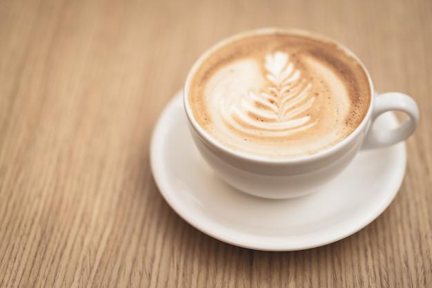 木製の背景にホットコーヒーカプチーノラテアート