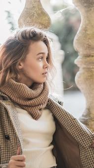 秋の街でポーズをとって、スタイリッシュな服を着て、長い髪の美しい幸せな女の子。