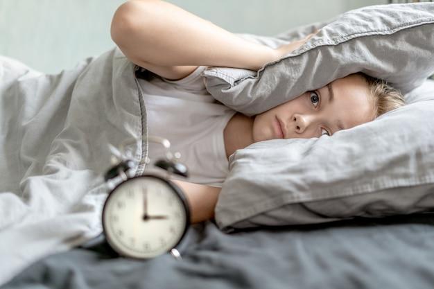 枕と目覚まし時計で彼女の耳を覆っている女の子