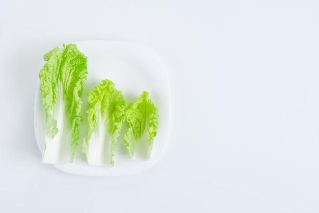 サラダは白いテーブルの上の白い皿の上の葉します。ダイエットのコンセプト