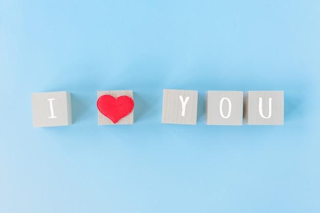 Я люблю тебя деревянные кубики с красным украшением в форме сердца на синем фоне стола и копией пространства для текста. любовь, романтика и с днем святого валентина концепция праздника