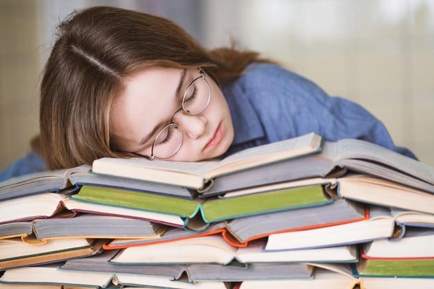 Подчеркнутый студент колледжа устал от тяжелого обучения с книгами в подготовке к экзаменам, перегружен школьной девочкой, уставшей от трудных занятий или слишком большого количества домашних заданий