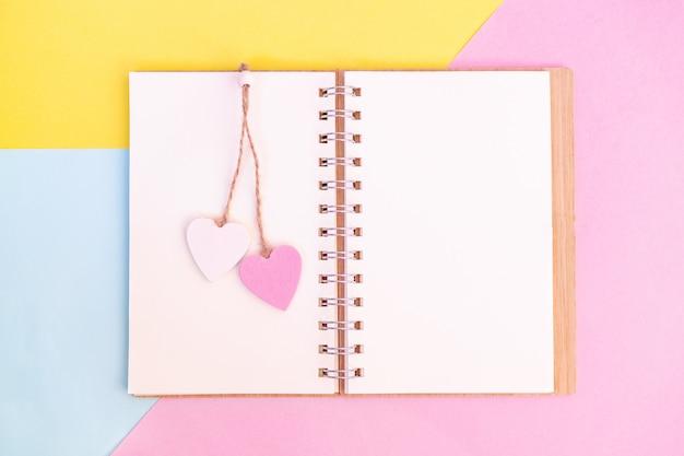 Откройте книгу с розовыми и белыми деревянными сердечками на них. отправьте сообщение своему любовнику в день влюбленных.