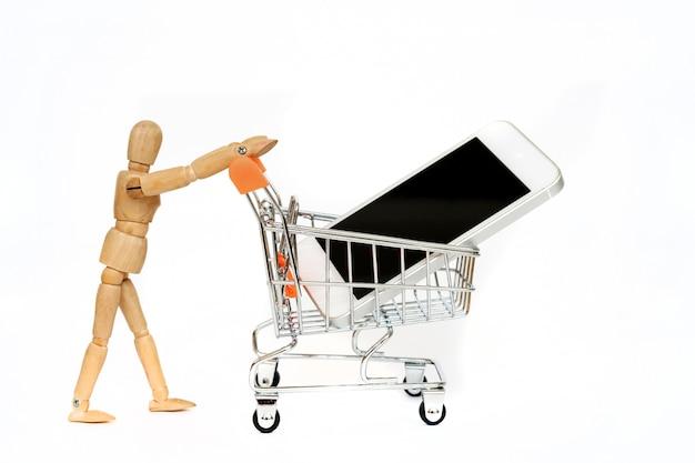 スマートフォンでショッピングトロリーを運ぶ木製のマネキン。ラインでは、分離されたモバイルショッピングの概念