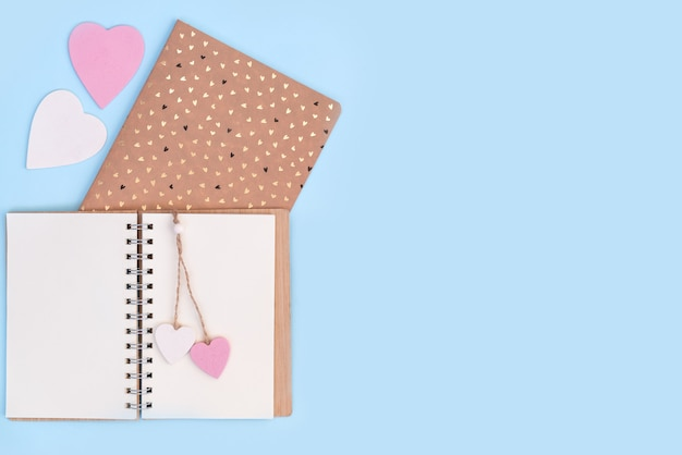 ピンクと白の木製の心を持つノートブック。バレンタインの日に恋人にメッセージを送ってください。