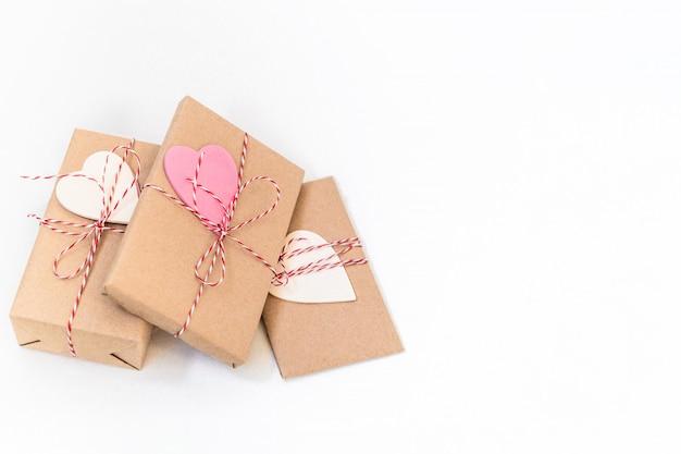 Подарочные коробки, завернутые в крафт-бумаги и украшенные красной лентой и деревянные сердца на белом фоне. день святого валентина, свадьба или другие праздничные украшения фона