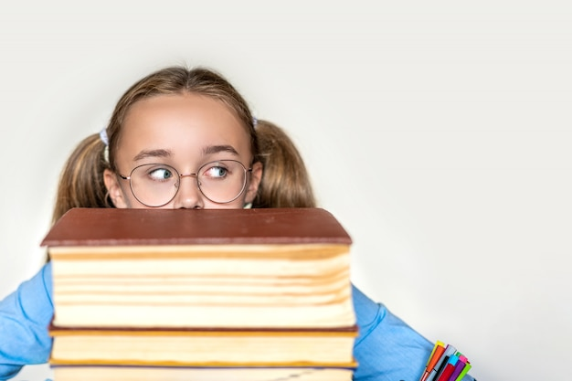 Подчеркнутая школьница, усталая от усердного обучения с книгами в подготовке к экзаменам, перегруженная старшеклассница, измученная трудными занятиями или слишком большим домашним заданием