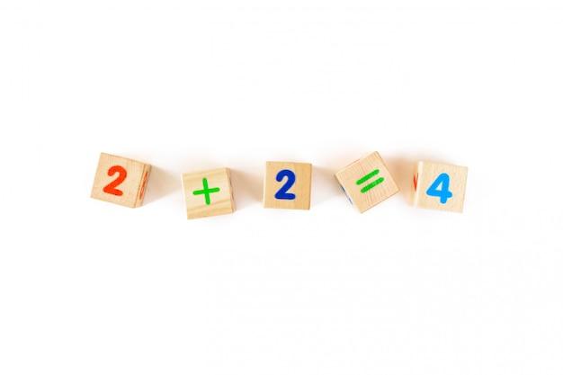 白い背景の上の数字で子供のおもちゃ木製カブス。木製ブロックの開発。子供向けの自然で環境に優しいおもちゃ。上面図。平干し。コピースペース。