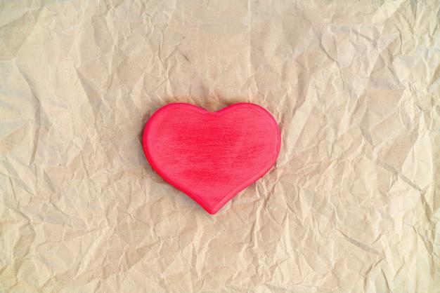 Красное деревянное любовное сердце на открытой тетради на синем фоне