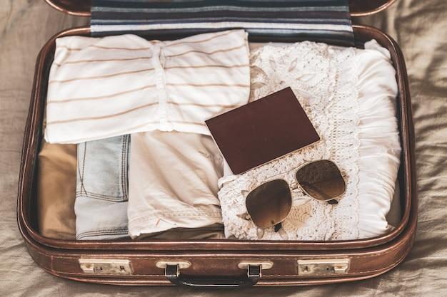 服、アクセサリー、パスポート、旅行、休暇の概念と旅行者のバッグを開く