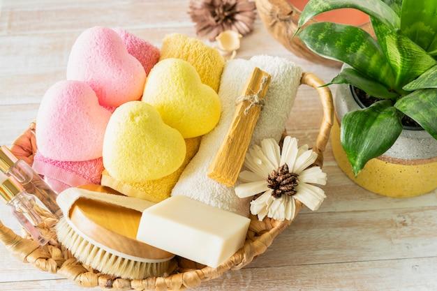 黄色とピンクのハート型のバスボム、ボディブラシ、美容液、パロサント、タオル、花でリラックスできるバスアクセサリー