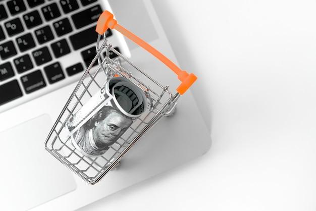 ノートブックコンピューター上のドル通貨で小さなショッピングカート。ショッピングのオンライン金融の概念。