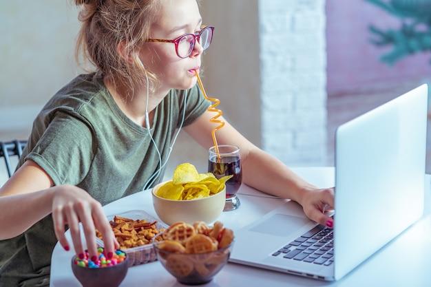 女の子はコンピューターで働き、ファーストフードを食べる